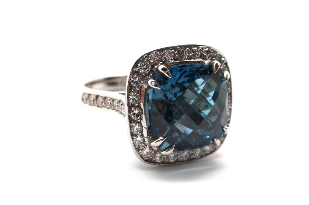 Checkerboard faceted cushion cut London blue topaz claw set above a halo of diamonds on a white gold band