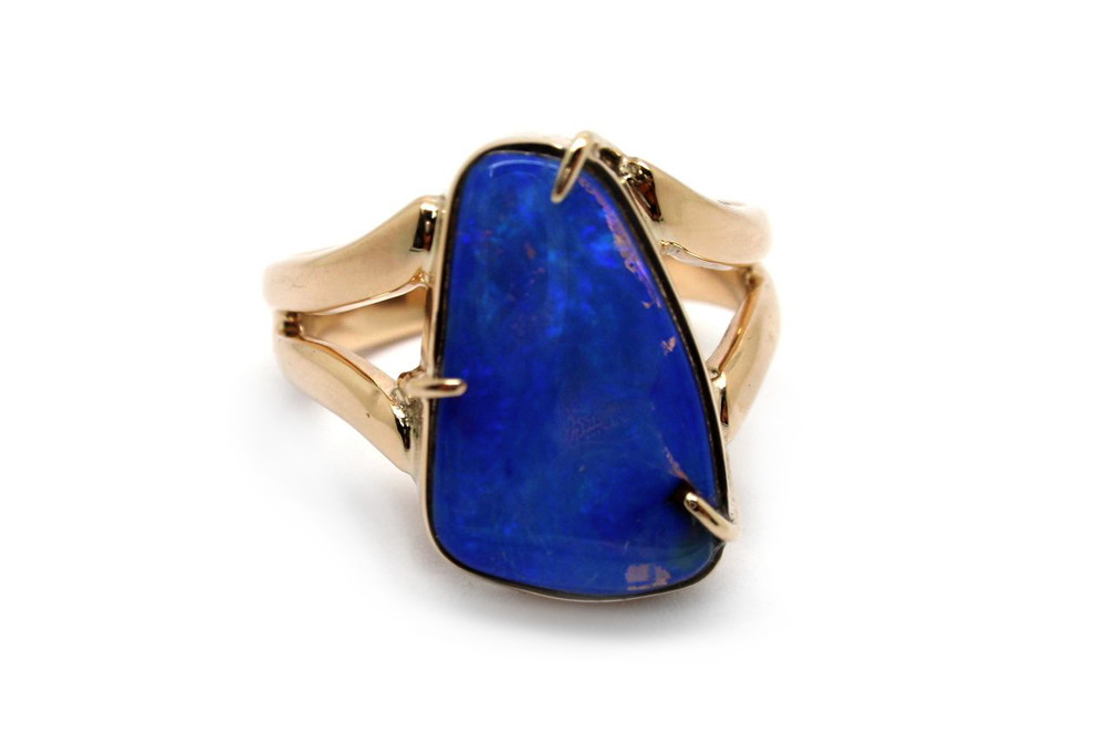 Solid black boulder opal claw set into yellow gold split band ring
