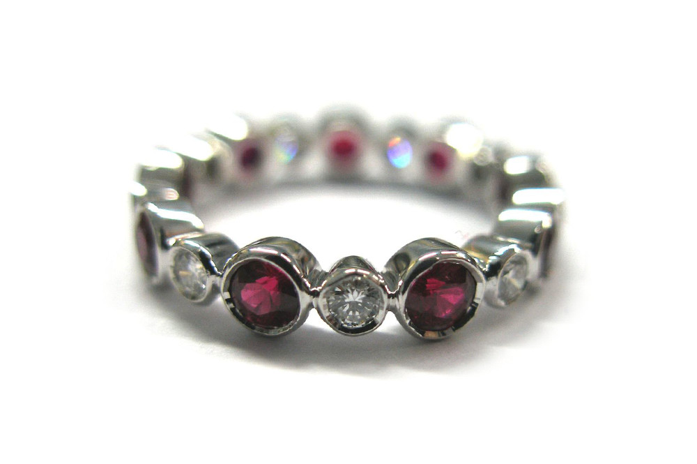 Brilliant cut round diamond and ruby bezel set ring