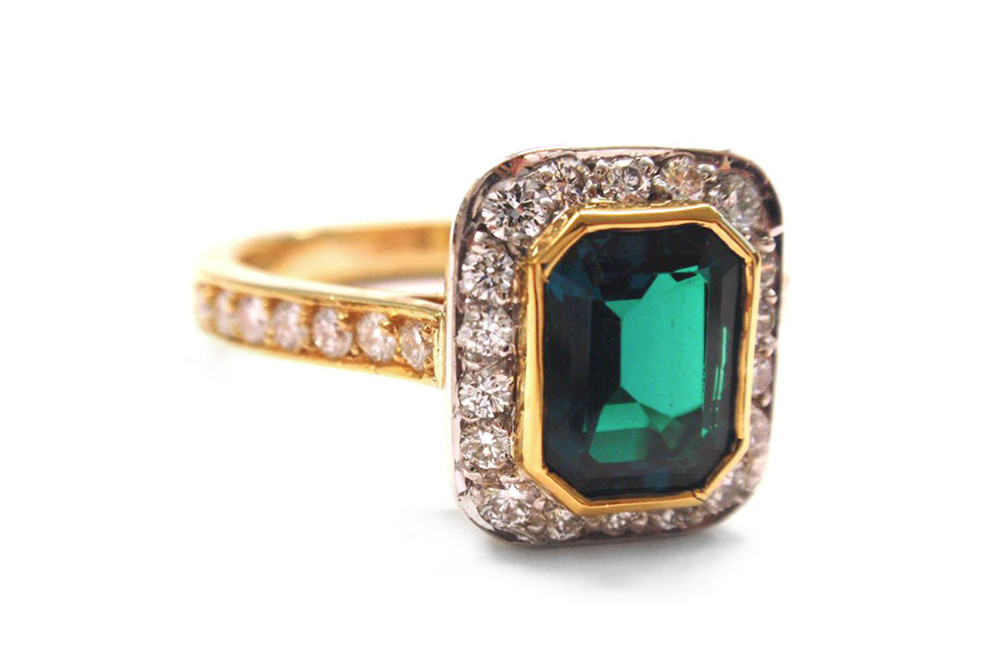 Emerald cut emerald, bezel set with halo of brilliant cut diamonds surrounding and a yellow gold pave set diamond band