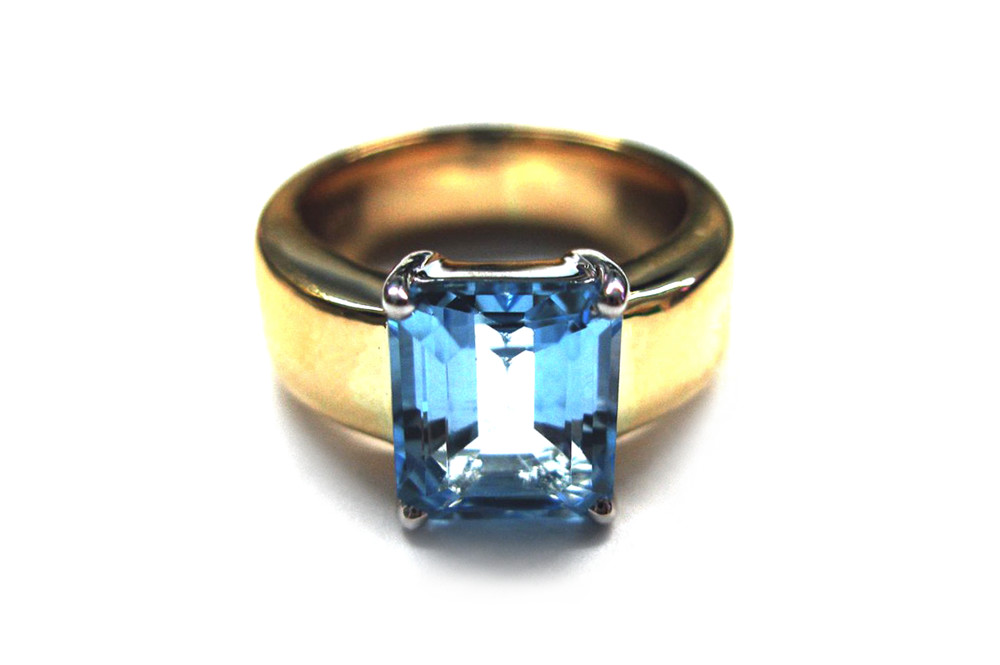 Emerald cut light blue topaz claw set over wide yellow gold band