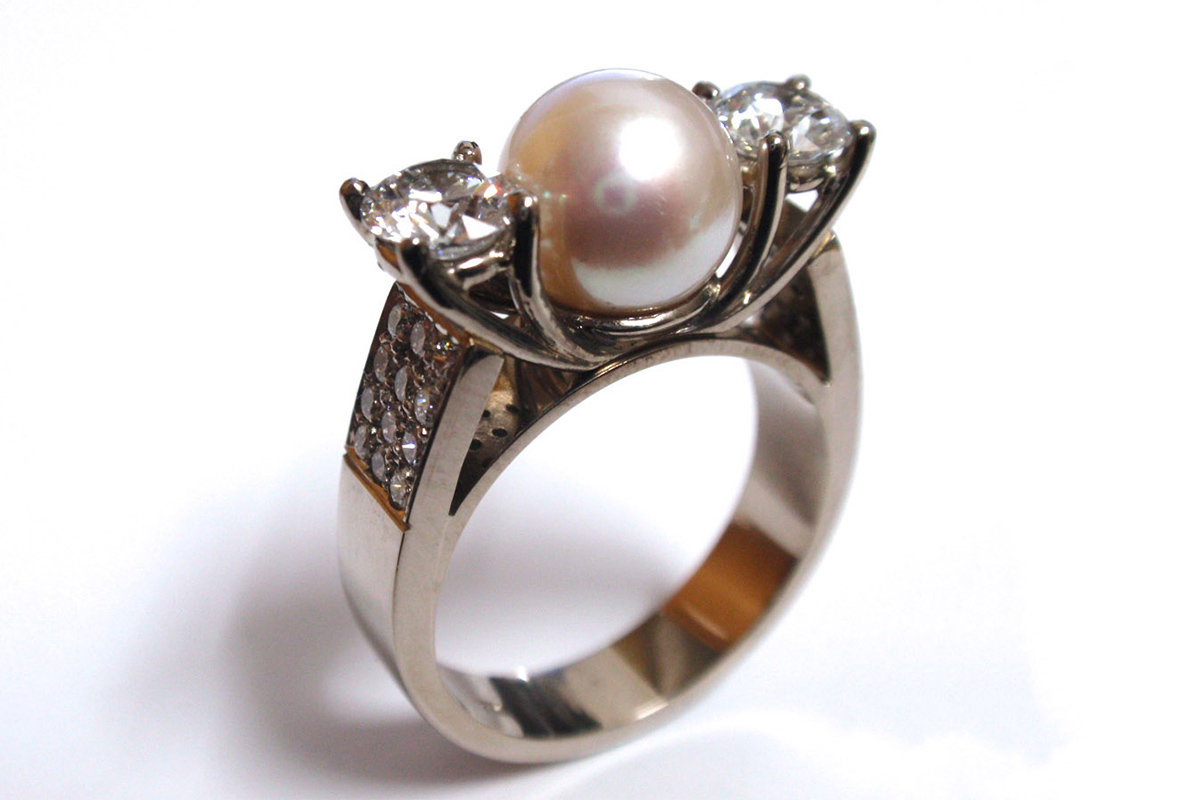 South sea pearl set in between claw set brilliant cut round diamonds with an upswept pave set white gold band