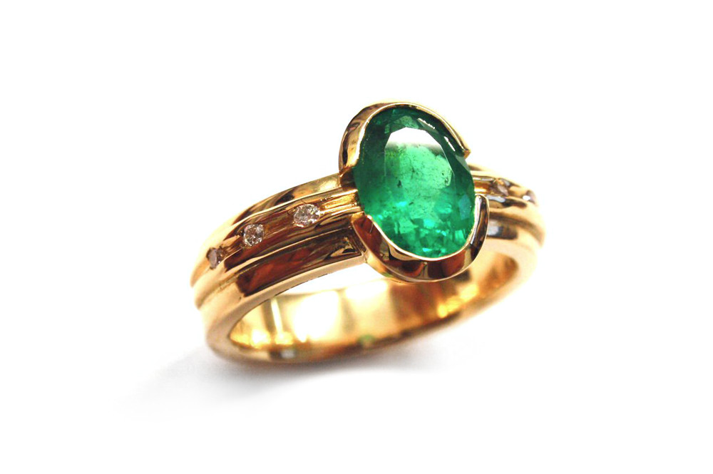 Oval natural emerald split bezel set with small brilliant diamonds set into yellow gold band