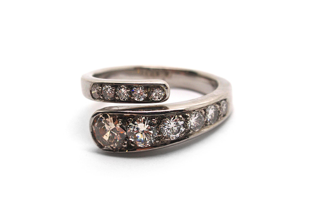 Created from a selection of inherited pieces this cross over ring has a champaign and white diamonds tapering in size