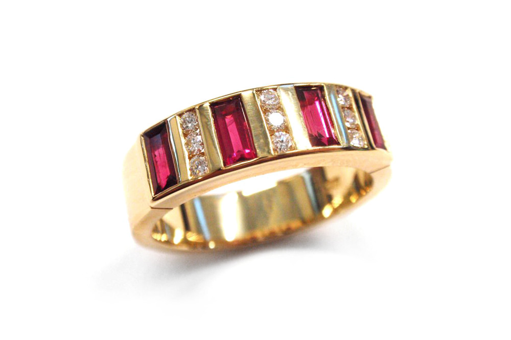 Natural baguette rubies set in between pave round diamonds in a yellow gold band