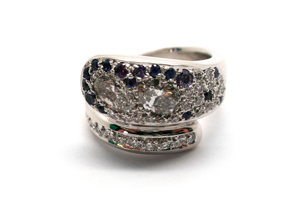 Oval and brilliant cut diamonds pave set in a overlapping style ring with purple sapphires
