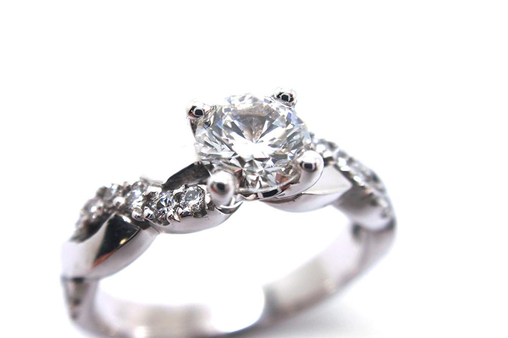 Brilliant cut diamond with a woven diamond band in white gold