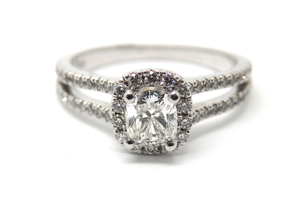 Split band claw set engagement ring with a cushion cut diamond surrounded by brilliant cut stones