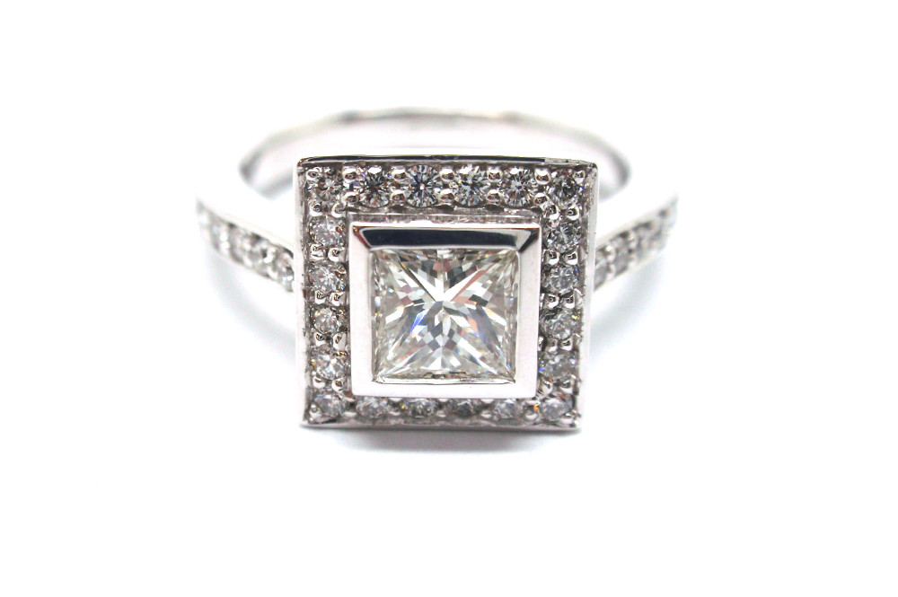 Princess cut diamond surrounded by a diamond halo and diamond shoulders set in white gold
