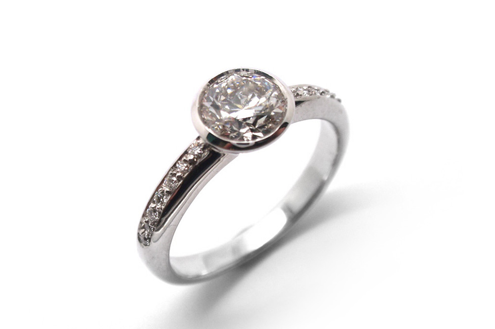Bezel set diamond with diamond pave shoulders in white gold