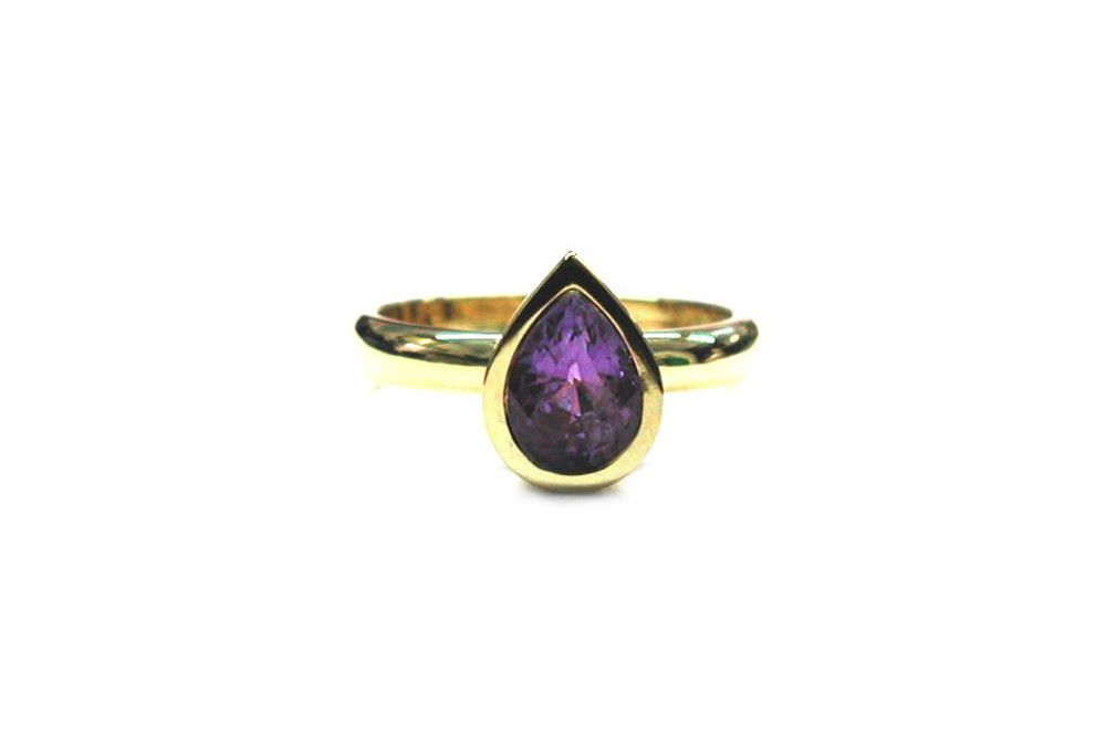 Pear shaped purple sapphire bezel set in yellow gold ring