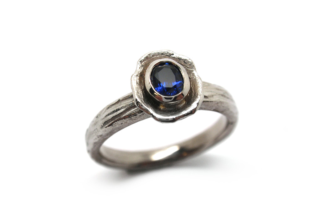 Natural blue sapphire bezel set in a nest stylised ring with a bark satin finish band