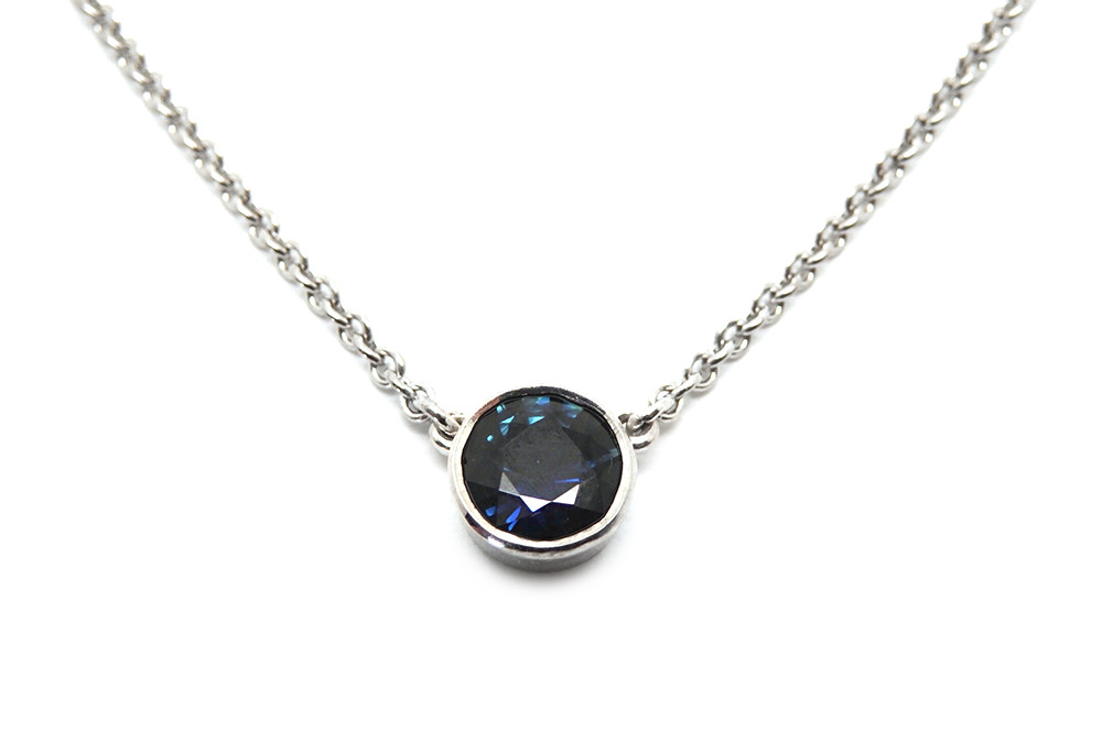 Bezel set round cut sapphire pendant attached onto fine trace chain