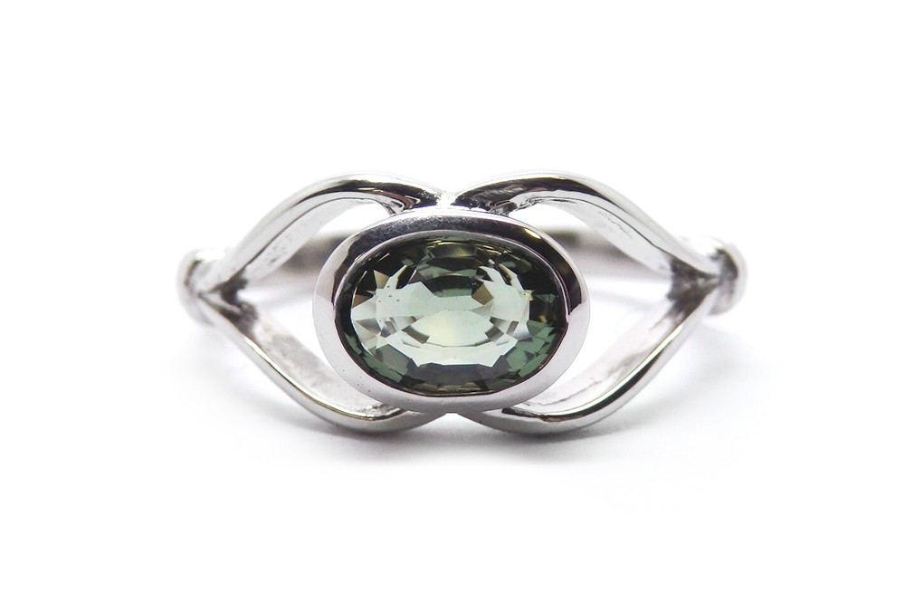 Natural green oval sapphire bezel set into open band ring