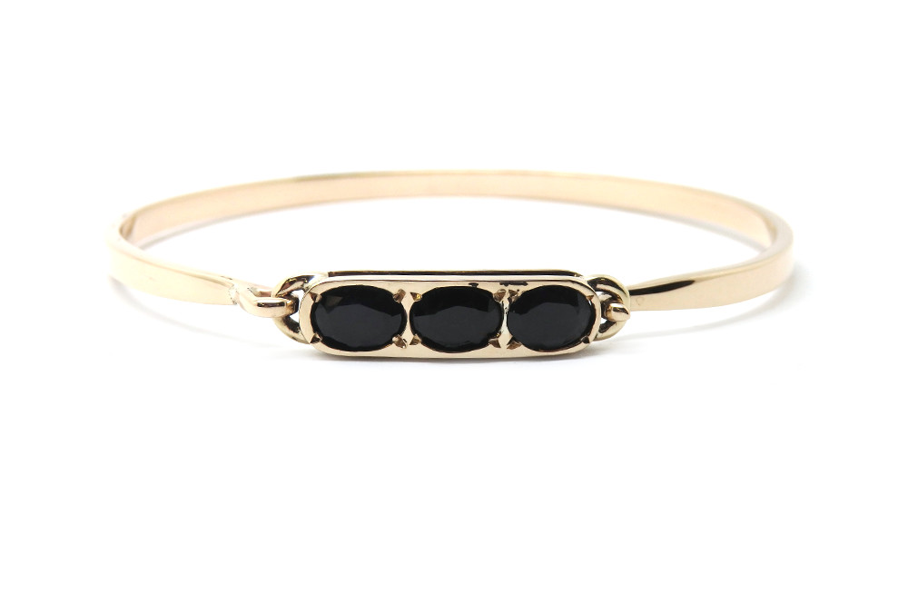 Oval dark sapphire grain set into solid bar with an open bangle