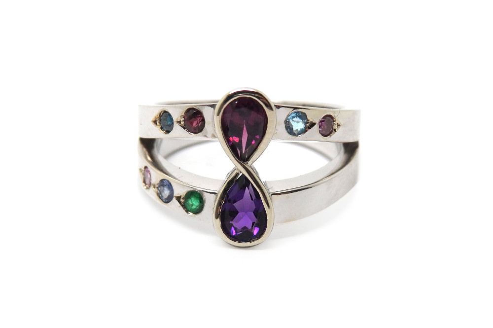 A family birthstone ring with parents in the eternal center setting and children and grand children on each band