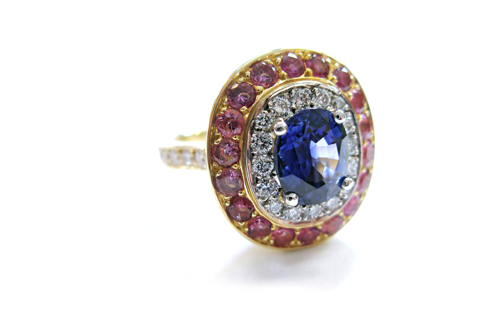 Claw set blue sapphire with surrounding halo of brilliant cut diamonds and pink coloured sapphires pave set with diamond band