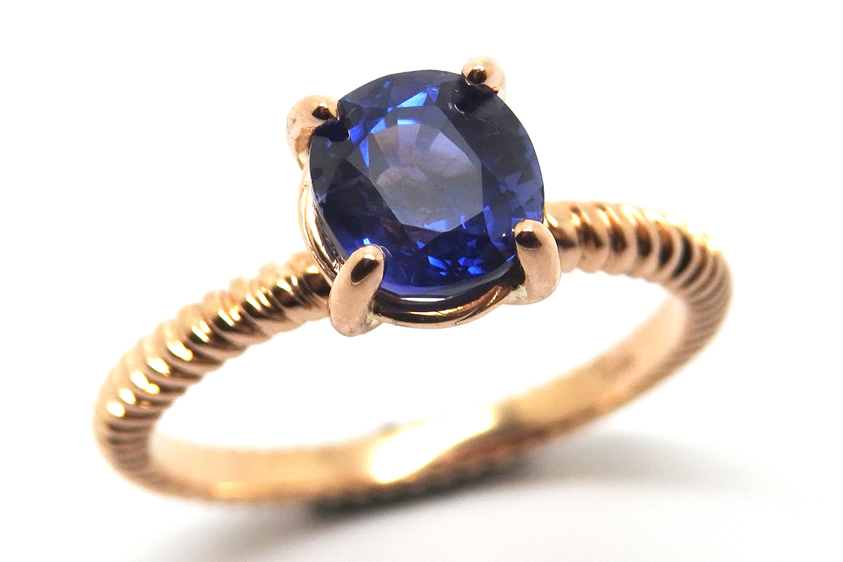 Fine twisted band and claw set sapphire ring