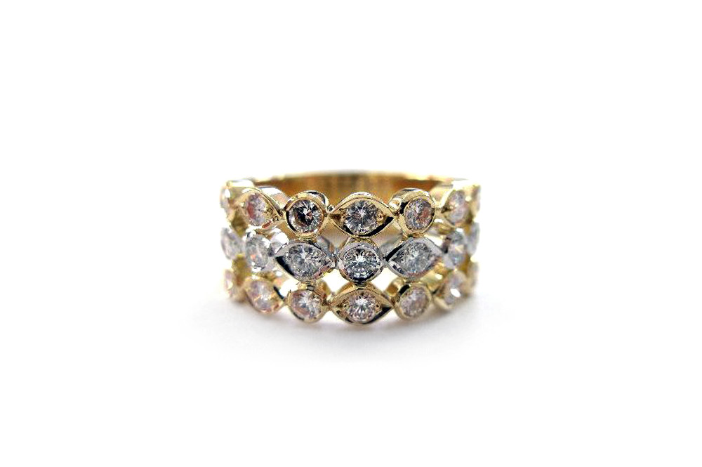 Round brilliant cut diamonds bead set into three yellow and white gold marquise shaped rows