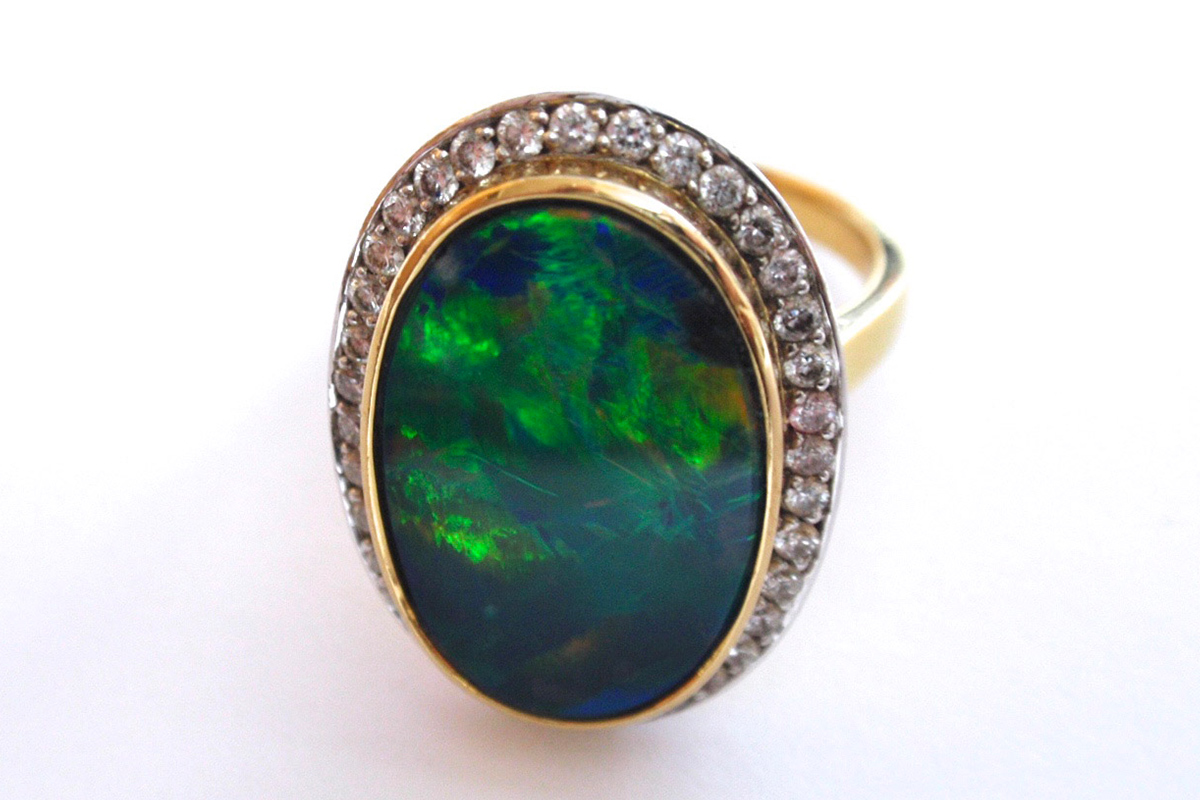 Bezel set opal with a halo of bead set diamonds
