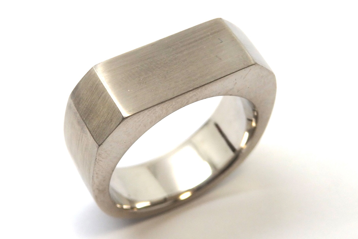 Hand carved men's wedding ring with a solid angled top, satin finished