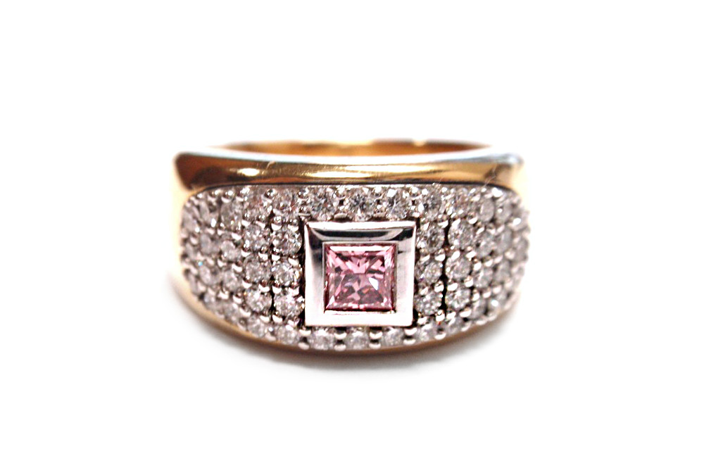 Princess cut pink diamond bezel surrounded by bead set brilliant cut diamonds inlayed into a yellow gold band