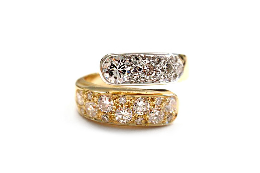 Multi sized round brilliant cut diamonds set into the ends of yellow and white gold cross over band