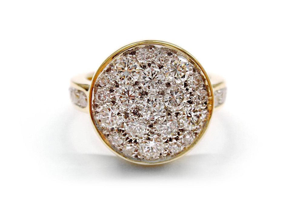 Multi sized round diamonds set into a round white gold disc framed in a yellow gold bezel ring