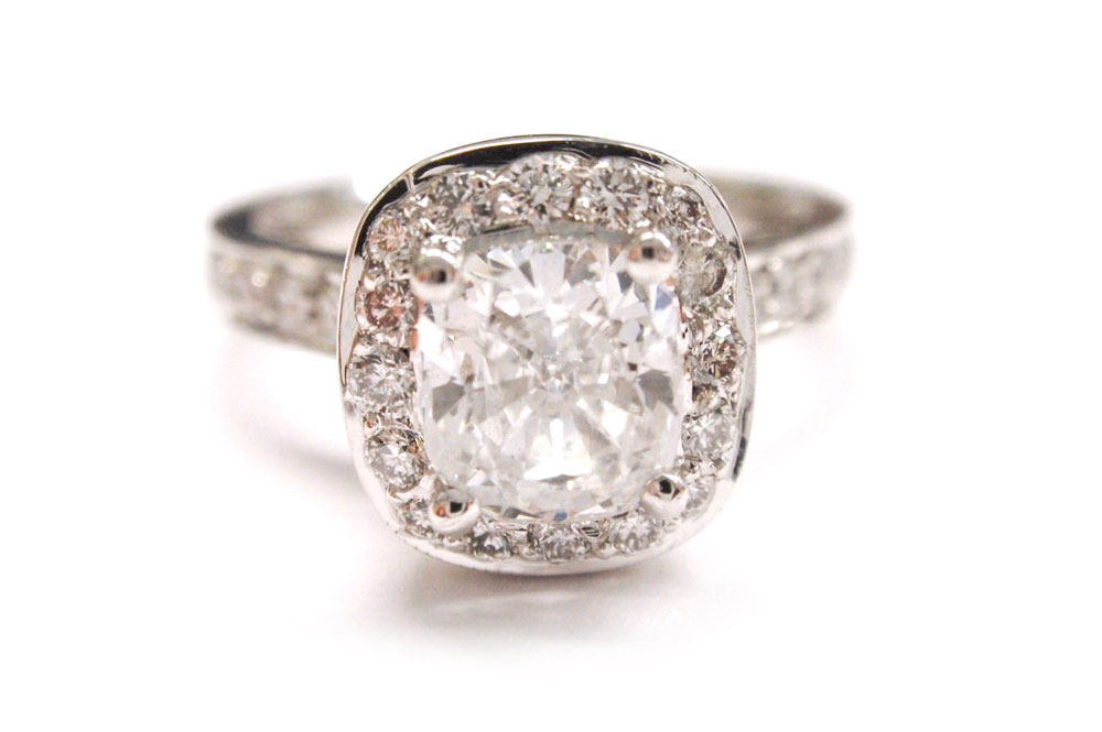Cushion cut center diamond claw set with surrounding halo of small round diamonds pave set into white gold metal with shoulder stones in the band
