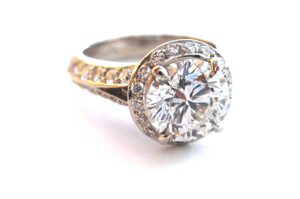 Brilliant cut round diamond claw set suspended over a circle of small round diamonds pave set with a split pave set diamond band