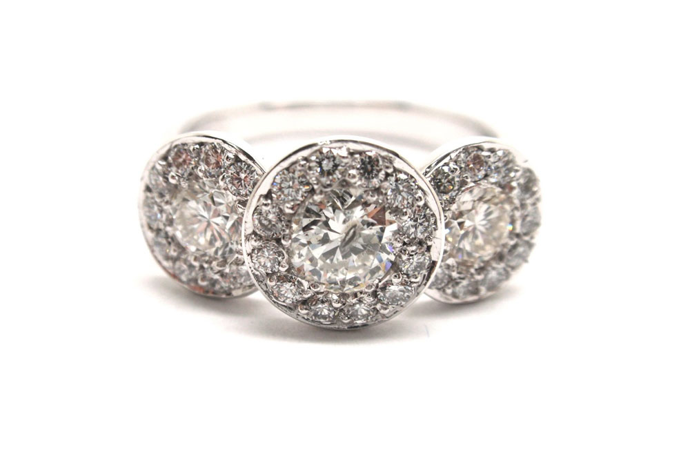 Three brilliant cut round diamonds surrounded with smaller round diamonds pave set into white gold band