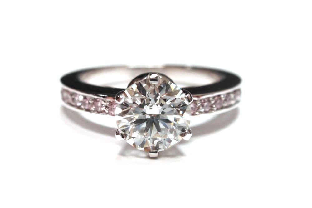 Six claw brilliant cut round diamond with pink diamonds pave set into band