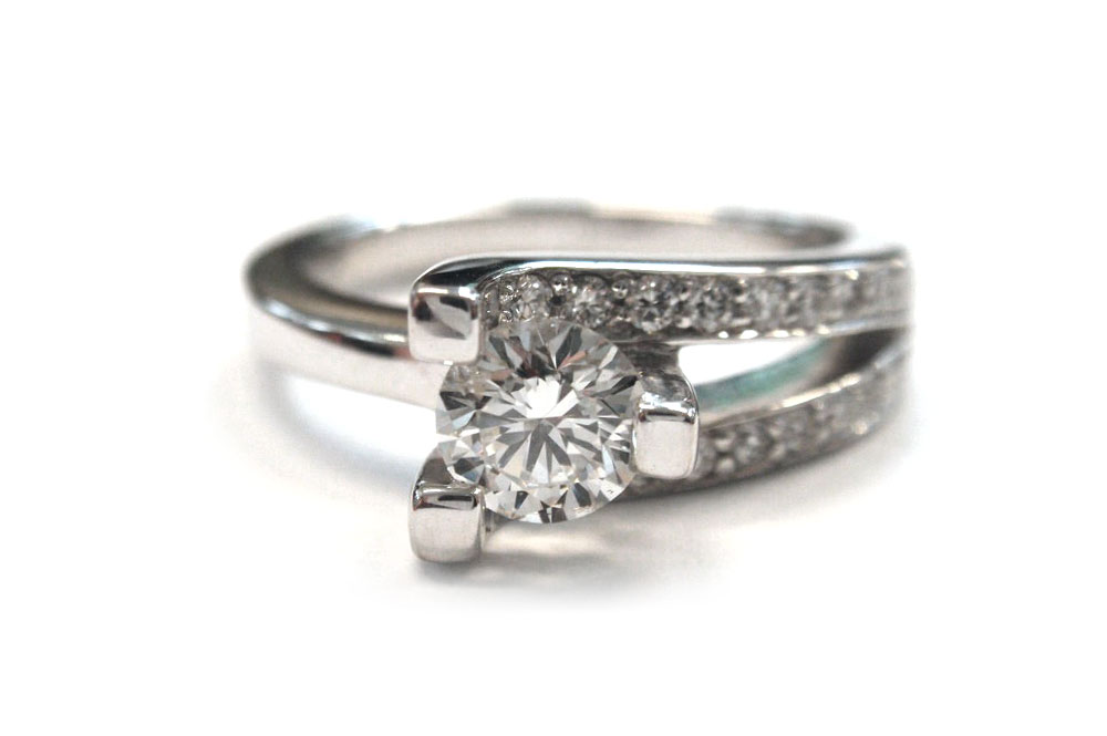 Brilliant cut round diamond set into three claws with three bars two pave set with smaller diamonds