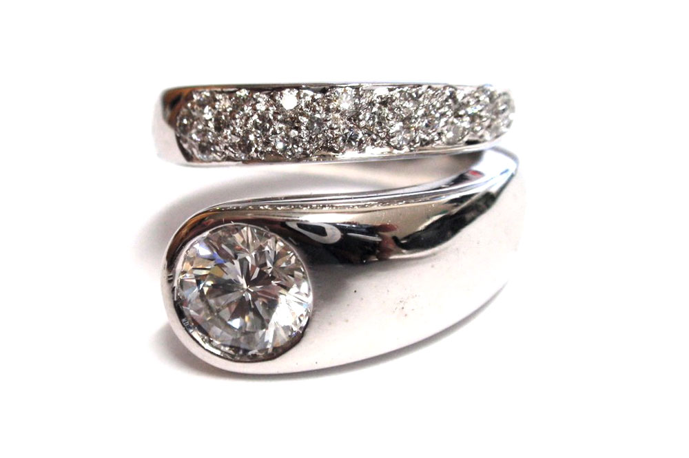 Hammer set brilliant cut round diamond with small round diamonds pave in opposite side of wrap around ring