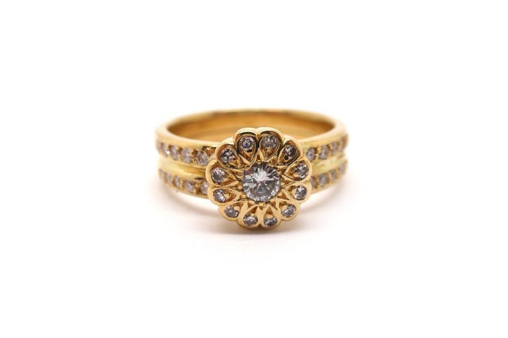 Round brilliant cut diamonds bead set into a scalloped circle with a two row diamond band