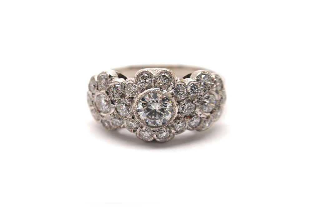 Brilliant cut round diamonds with surrounding smaller diamonds scalloped set with mill edging