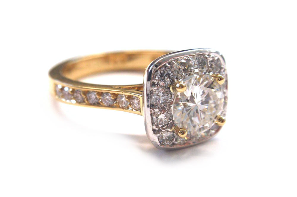 Brilliant cut round diamond claw set with smaller diamonds halo set in a cushion cut shape with pave diamonds in band