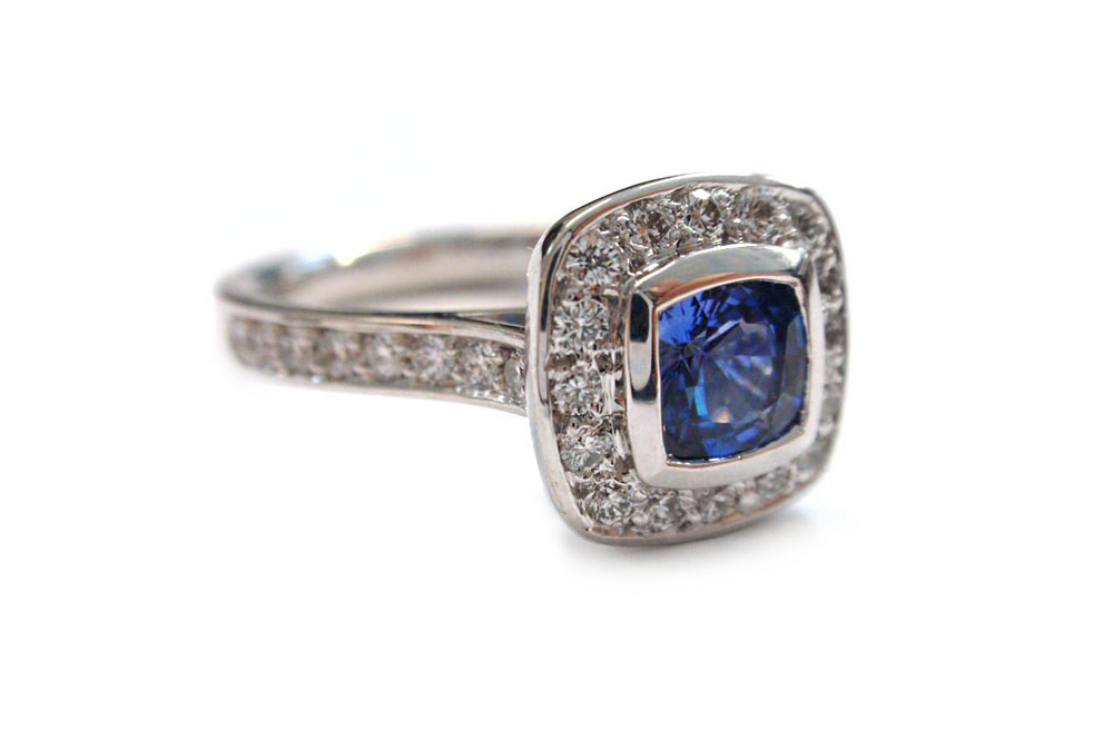 Cushion cut blue sapphire bezel set with a halo of pave diamonds