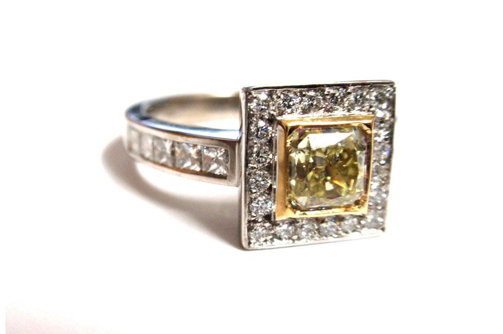 Asscher cut yellow diamond frame set with round white diamonds and a diamond band