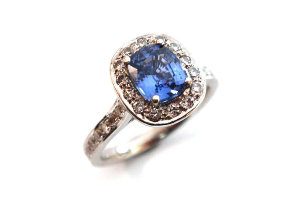 Cushion cut blue sapphire claw set with surrounding white round diamonds pave set