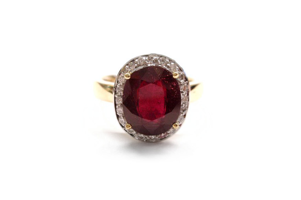 Oval cut ruby claw set with a halo surround of pave brilliant cut diamonds