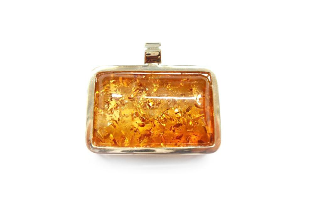 Amber cabochon bezel set in gold frame pendant